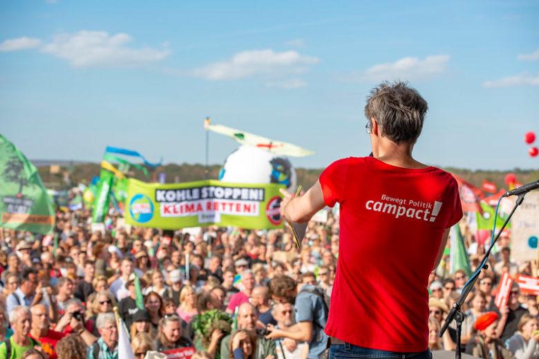 Foto: Eine Person im Campact-T-Shirt steht vor einer Menschenmenge mit verschiedenen Transparenten und redet ins Mikrofon. Jobs bei Campact: So können Sie Campact unterstützen