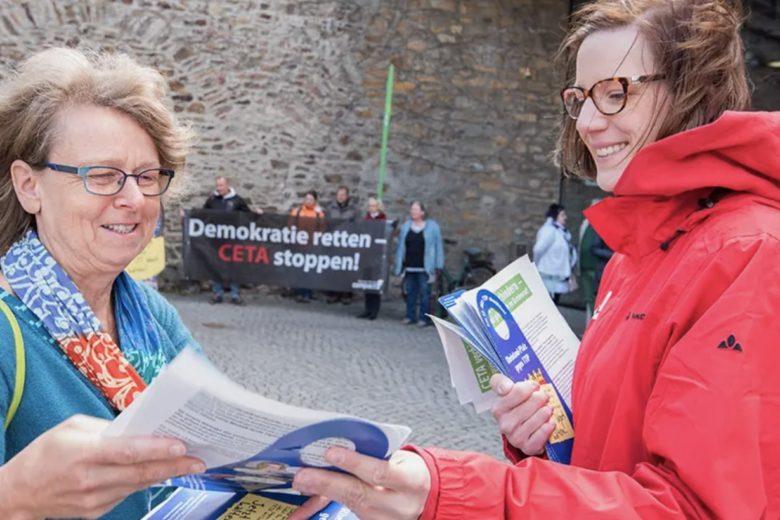 """Foto: Zwei Personen mit Infobroschüren stehen vor einer kleinen Gruppe, die ein Transparent mit der Aufschrift: """"Demokratie retten-CETA stoppen!"""" halten. Sie haben Fragen zu Campact? Fragen und Antworten finden Sie in unseren FAQs"""