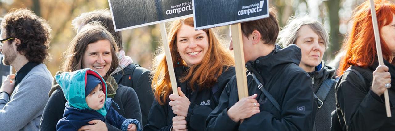 Campact für Fortschritt - Menschen demonstrieren mit Campact-Schildern
