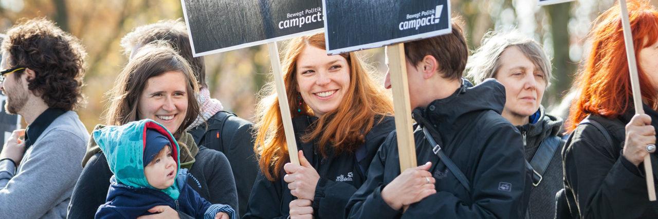 Foto: Ein paar Personen mit Pappschildern von Campact. Campact ist eine Bürgerbewegung, mit der über 2 Millionen Menschen für progressive Politik streiten.