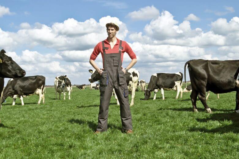 Kampagnen-Bild: Bauer steht auf einer Wiese zwischen grasenden Kühen. Campact-Appell: Mercosur stoppen, kein Billigfleisch in Massen