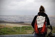Frau mit Rucksack und Protestschild sitzt vor Tagebau