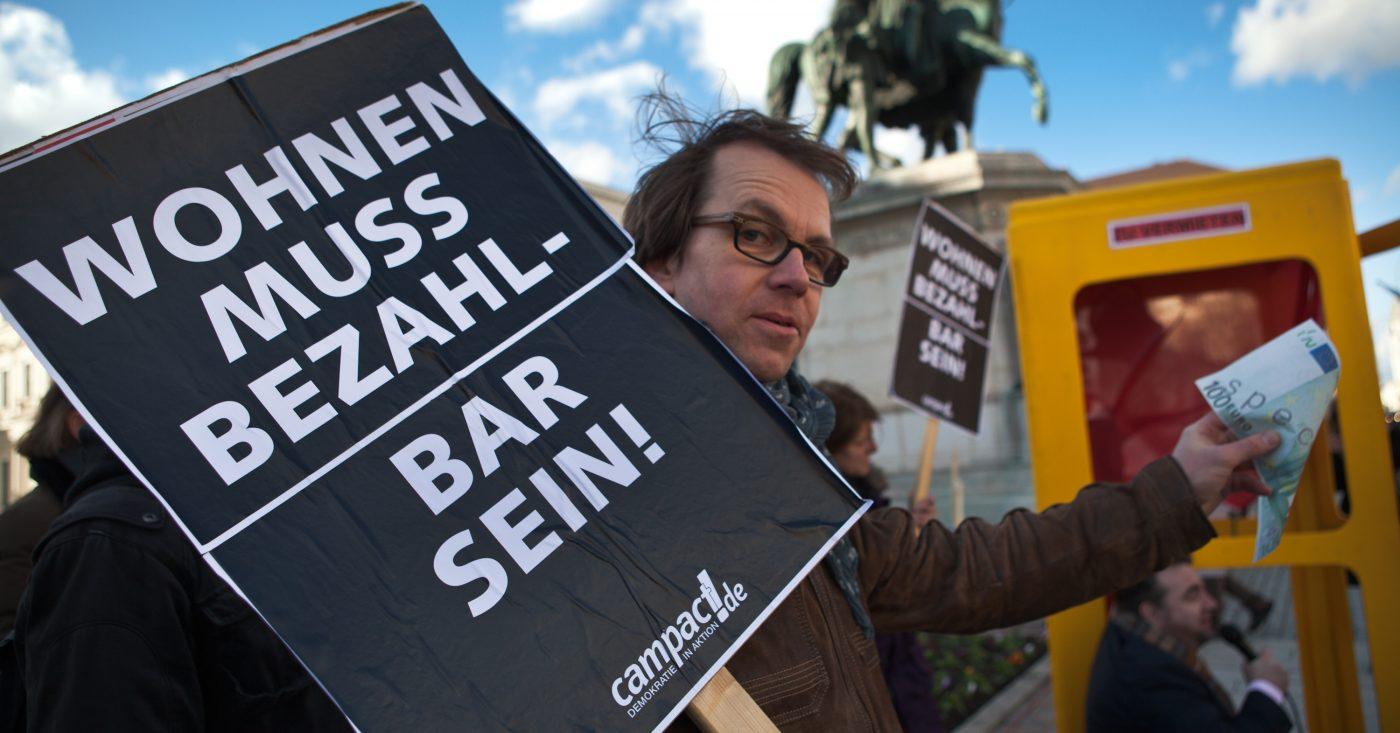 Ein Mann demonstriert für bezahlbaren Wohnraum in München