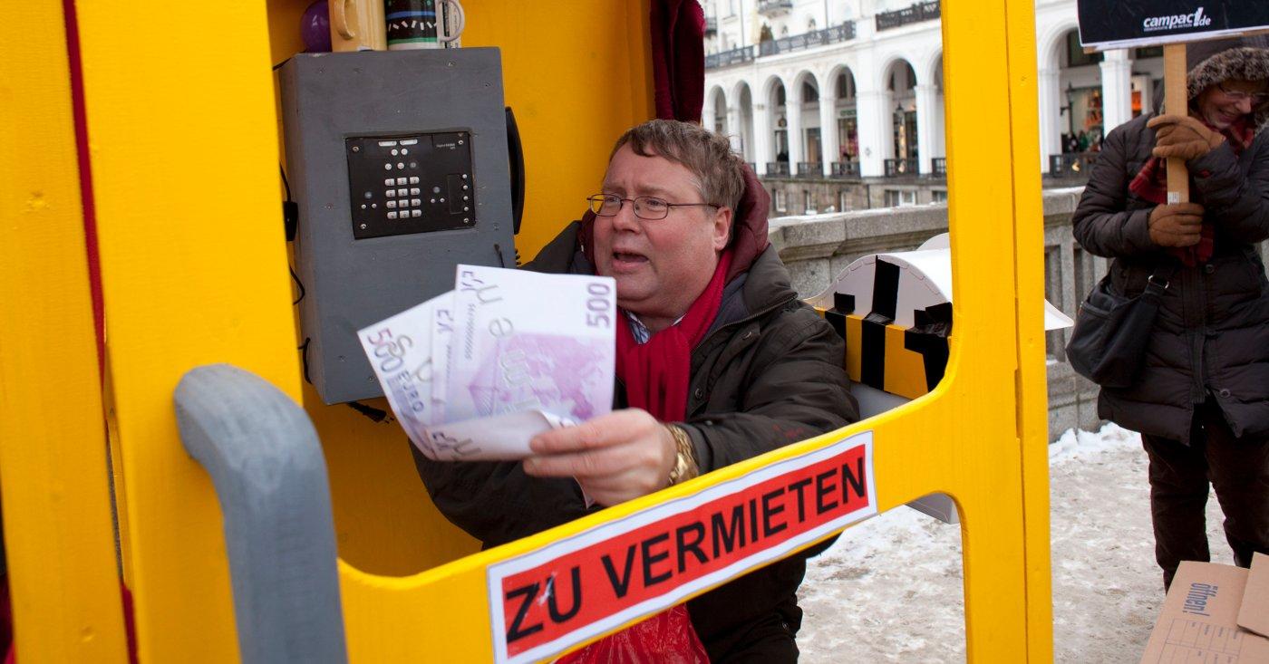 Ein Mann demonstriert in Hamburg für bezahlbaren Wohnraum in einer Telefonzelle