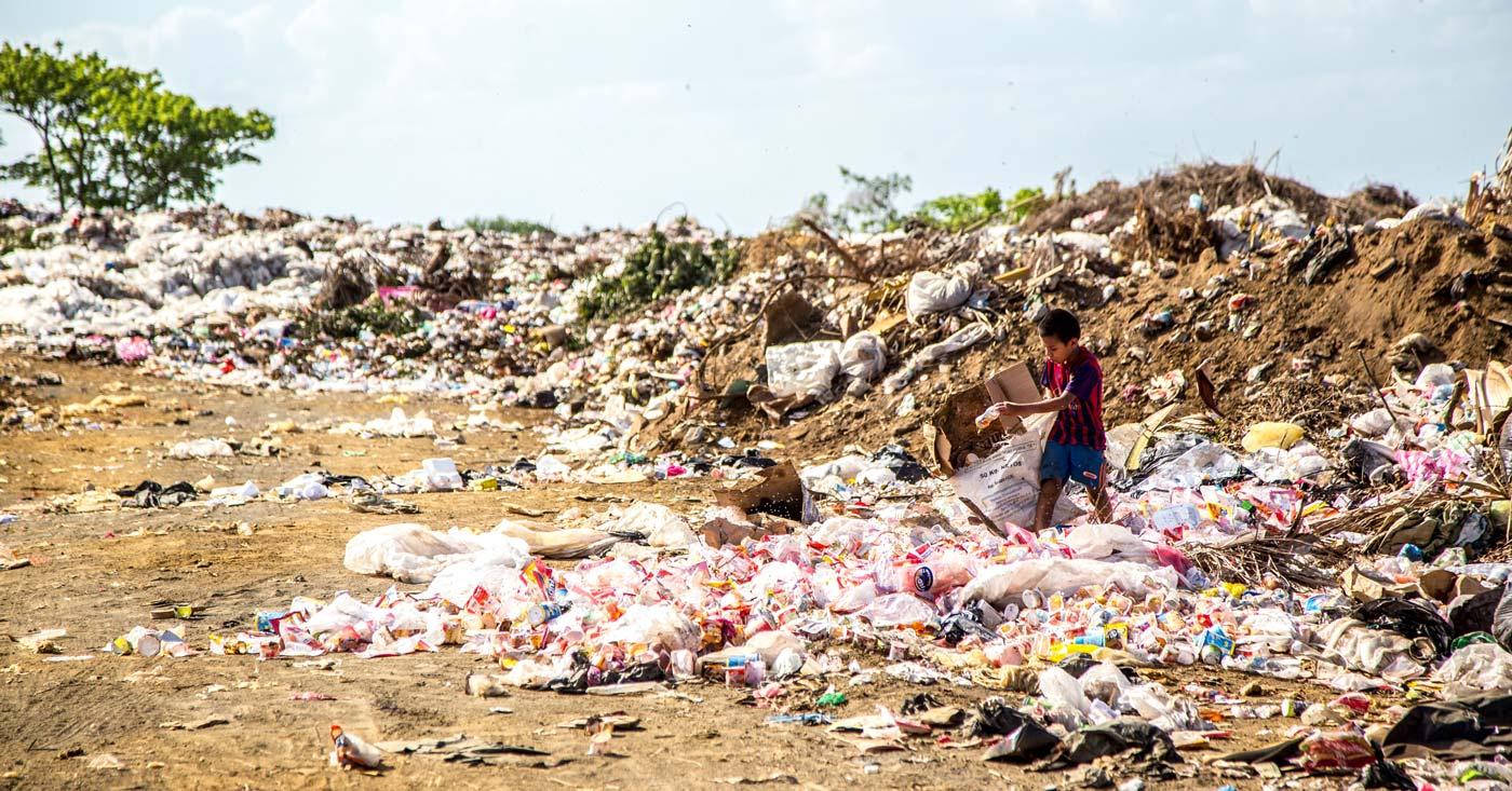 Ein kleiner Junge steht inmitten von Plastikbergen. Jetzt WeAct-Petition gegen Plastikexporte unterzeichnen