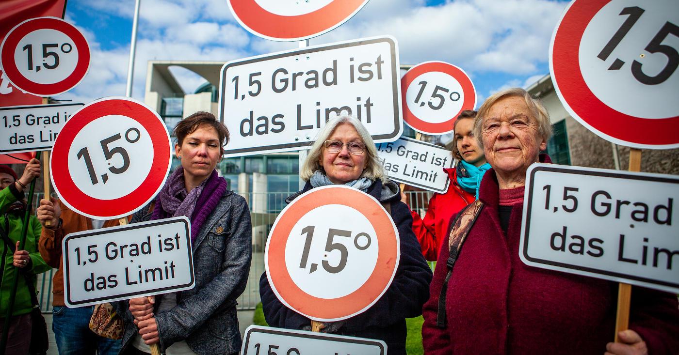 """Campact-Aktive demonstrieren mit Schildern """"1,5 Grad ist das Limit"""" für mehr Klimaschutz"""