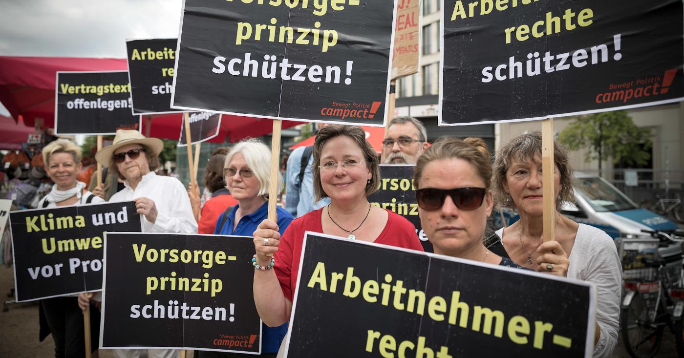 Menschen mit Plakaten demonstrieren gegen unfaire Handelsabkommen