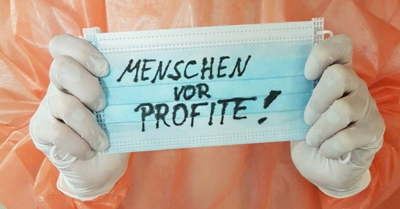 Zwei Hände halten eine Schutzmaske mit der Aufschrift: Menschen vor Profite!