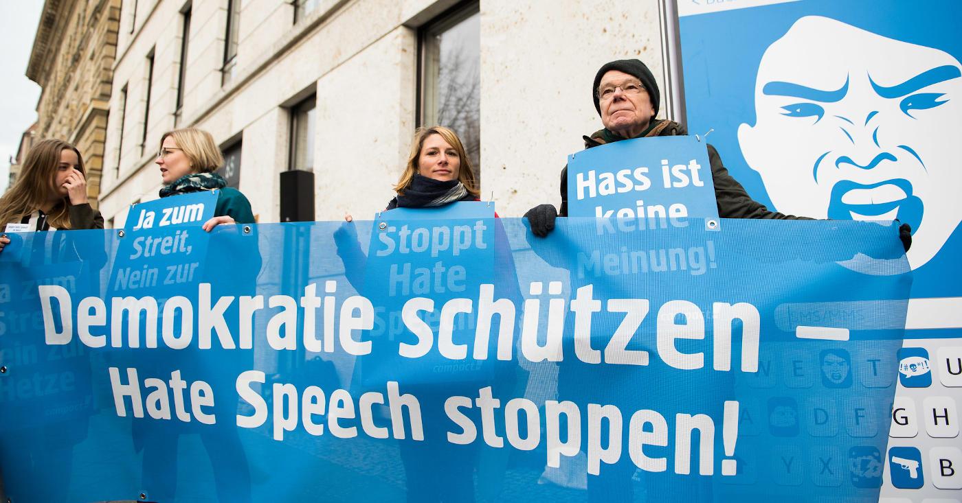Campact-Aktive fordern mit einem Banner: Demokratie schützen - Hate Speech stoppen!