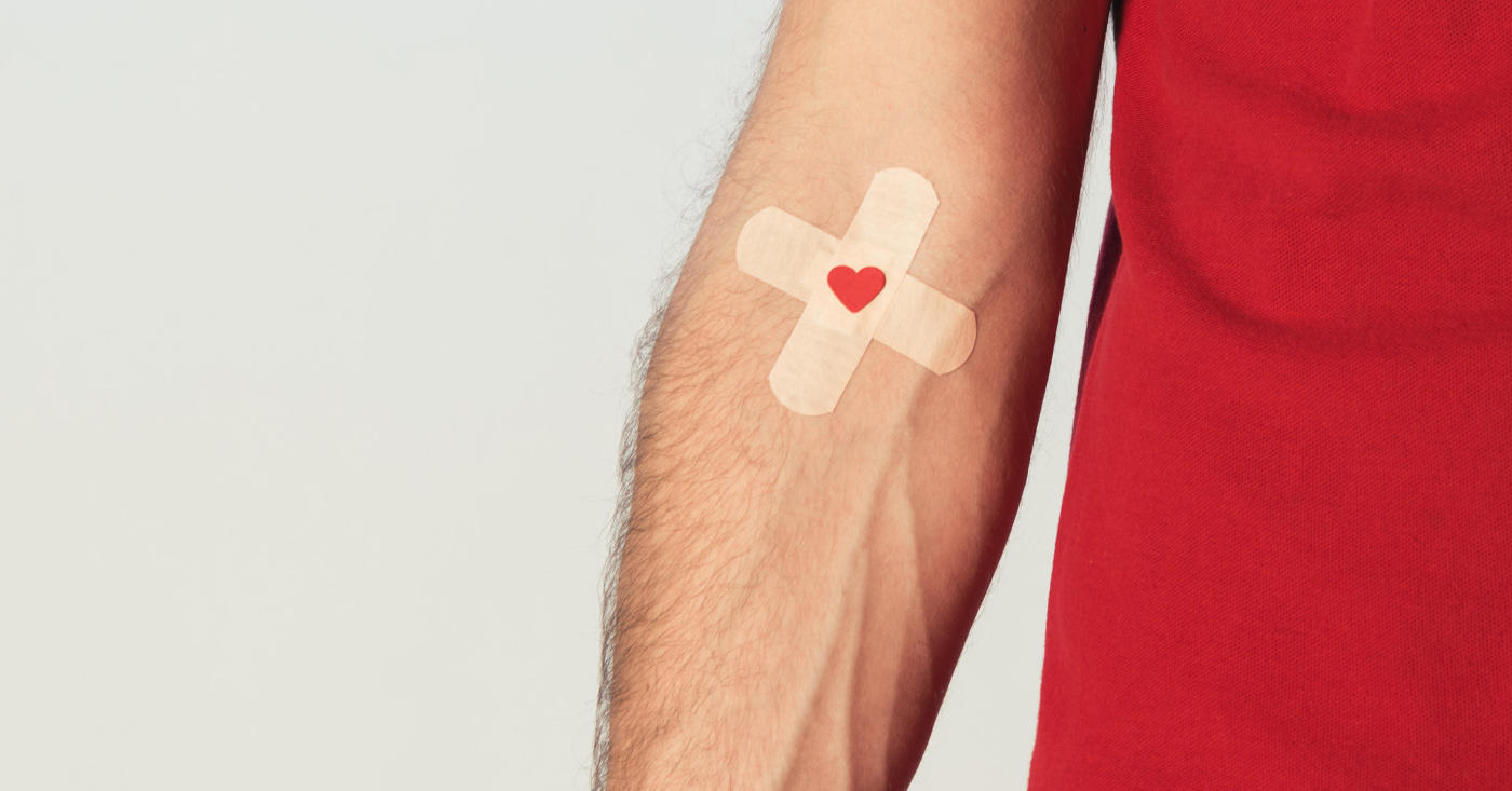Arm eines Mannes mit einem Pflaster in der Armbeuge. Auf dem Pflaster ist ein rotes Herz