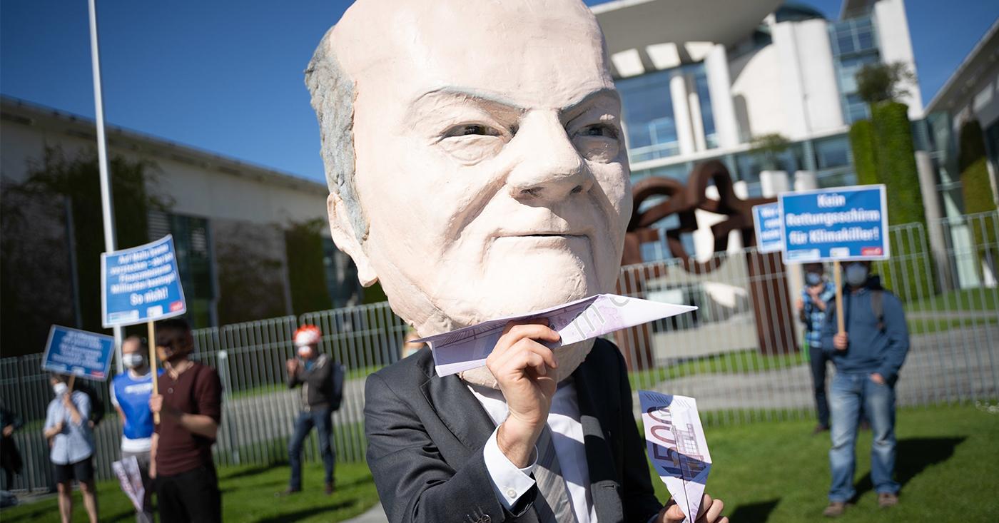 Mensch mit riesiger Olaf-Scholz-Maske hält Papierflieger aus 500 Euro Scheinen in der Hand