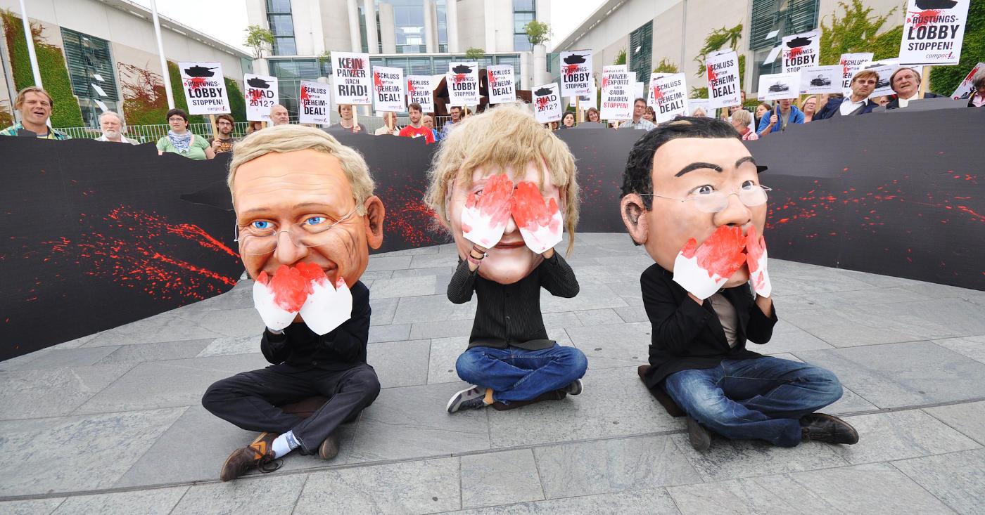 Drei Menschen mit Politikermasken sitzen vor Demonstranti*innen mit Plakaten. Eine*r hält sich den Mund zu, eine*r die Augen, eine*r den Mund.