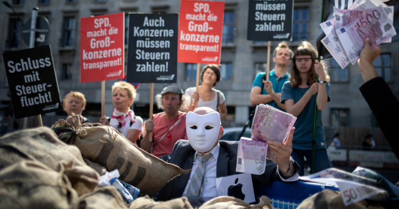 Mann Mit Maske hält bei einer Kundgebung mehrere 500-Euro-Scheine in der Hand