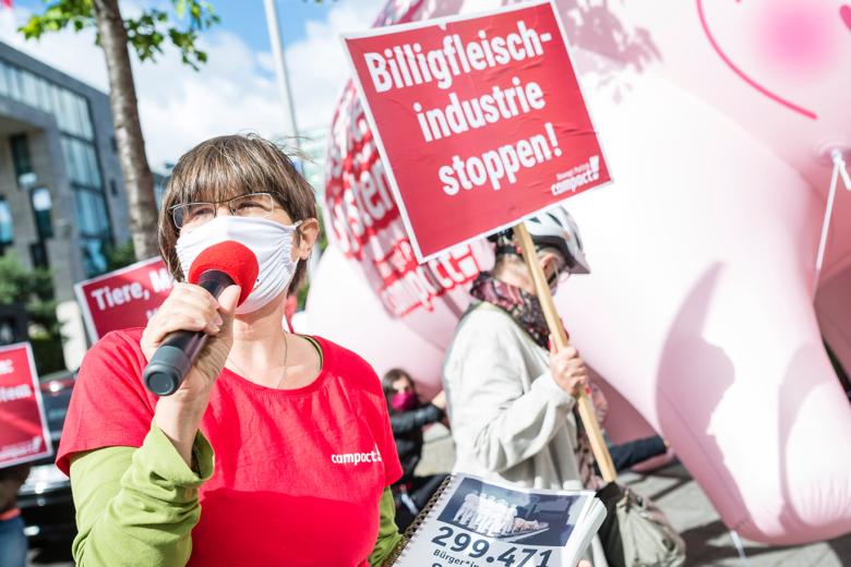 Campact-Aktion Billigfleisch: Person spricht in ein Mikrofon, im Hintergrund halten weitere Personen Schilder