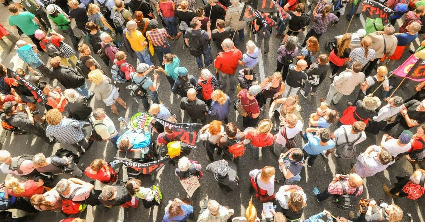 Eine Menschenmenge auf einer Demonstration ist aus der Vogelperspektive zu sehen - Die Schufa will die Konten von Millionen Verbraucher*innen ausspionieren - mit schwerwiegenden Folgen für ihre Kreditwürdigkeit, Campact startet einen Appell