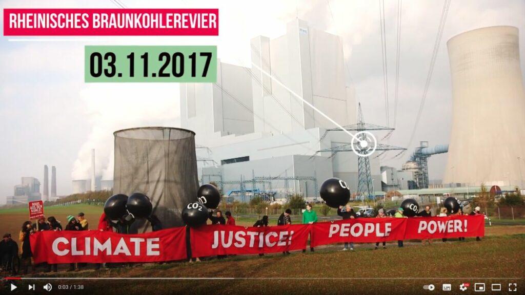 """Screenshot Youtube: Aktivisten stehen in einer Reihe vor dem rheinischen Braunkohlerevier und halten Banner mit der Aufschrift """"Climate, Justice, People, Power"""" sowie Ballons mit der Aufschrift CO2 hoch"""