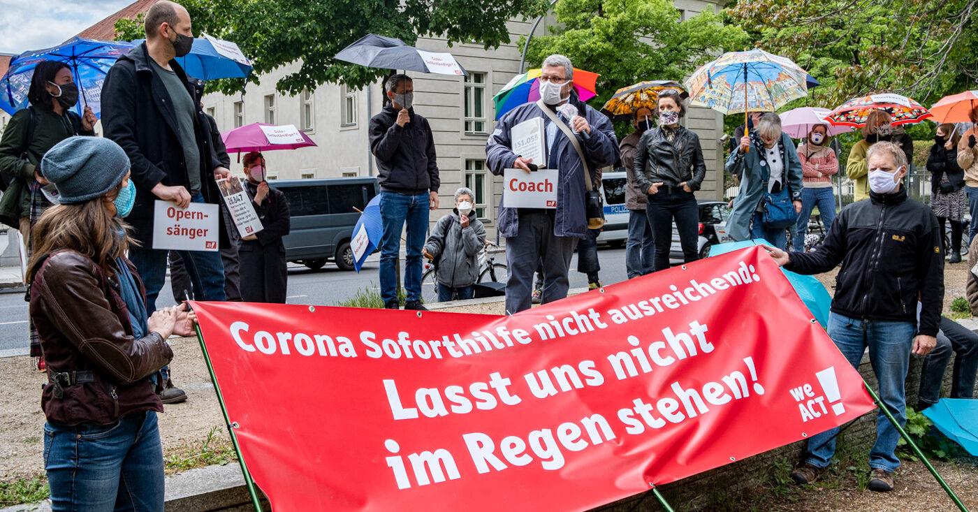 """Corona-Nothilfe: Mehrere Personen beim Protest, zwei Personen halten im Vordergrund einen WeAct Banner mit der Aufschrift """"Corona Soforthilfe nicht ausreichend: Lasst uns nicht im Regen stehen!"""""""