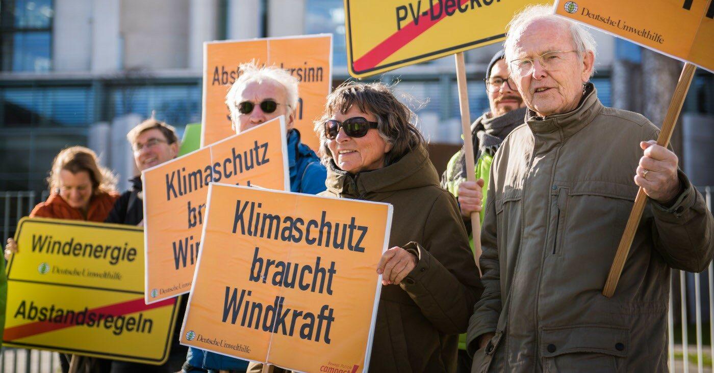 Windkraft NRW: Mehrere Menschen halten bei einem Protest Schilder in den Händen mit der Aufschrift Klimaschutz braucht Windkraft.