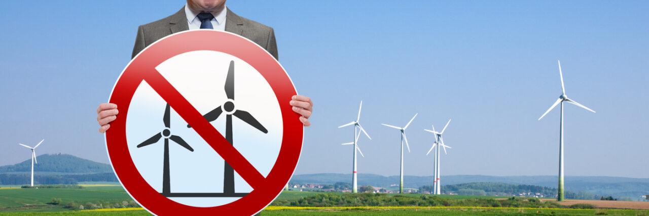 Windkraft NRW: Laschet hält ein rundes Schild in den Händen, auf dem Windkraft-Symbole rot durchgestrichen sind
