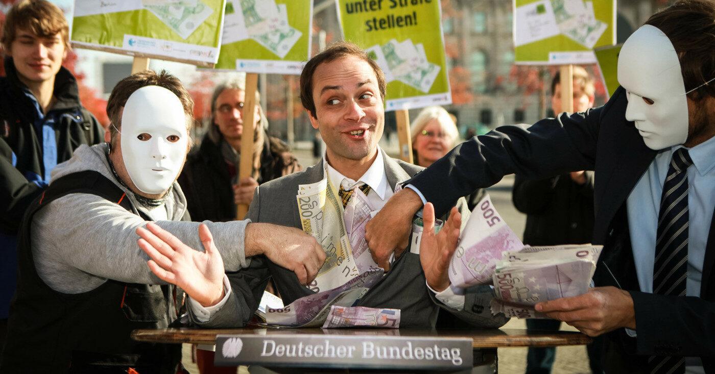 Darsteller bei Protest: 2 Personen mit weißer Maske stecken einer Person Geld in den Anzug, die vor einem Sprechpult vom Deutschen Bundestag steht. Kampagne Korruption bekämpfen!