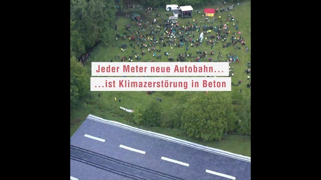 """Foto zum Thema """"Keine neuen Autobahnen! Das fordern wir im Bündnis mit einer spektakulären Banner-Aktion."""" Daneben sieht man sehr viele Personen in der Natur."""