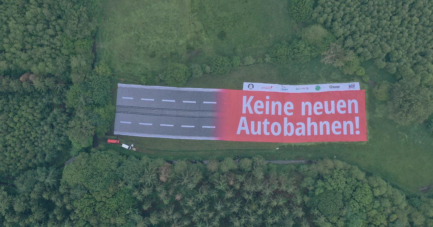 Ein riesiges Banner liegt in der Natur, wo die Küstenautobahn A20 gebaut werden soll. Es ist zu lesen: Keine neuen Autobahnen!