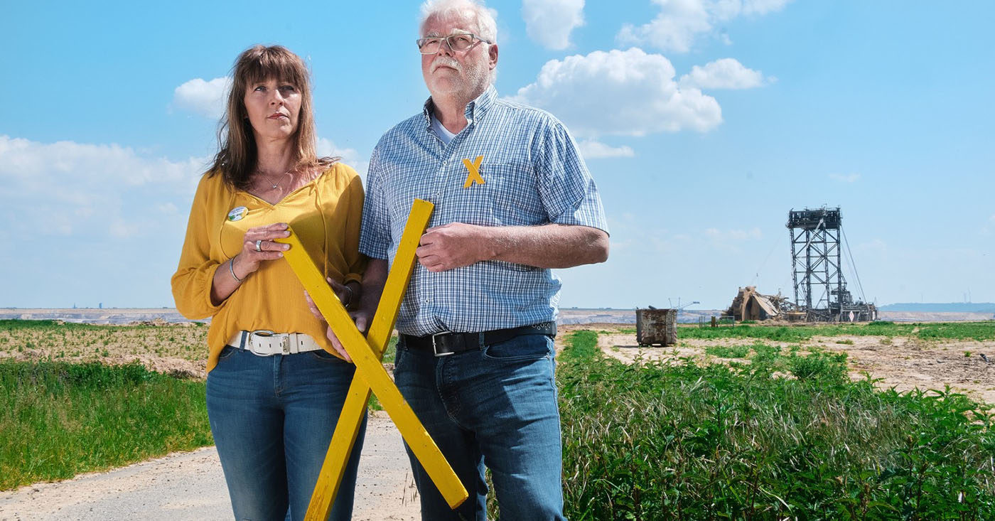Marita Dresen und Helmut Kehrmann wohnen am Tagebau Garzweiler II in Nordrhein-Westfalen. Sie halten ein großes gelbes X in der Hand. Mit ihrer WeAct-Petition fordern sie: Kein weiteres Dorf mehr für Kohle: Unterzeichnen Sie jetzt für Klimagerechtigkeit hier und überall