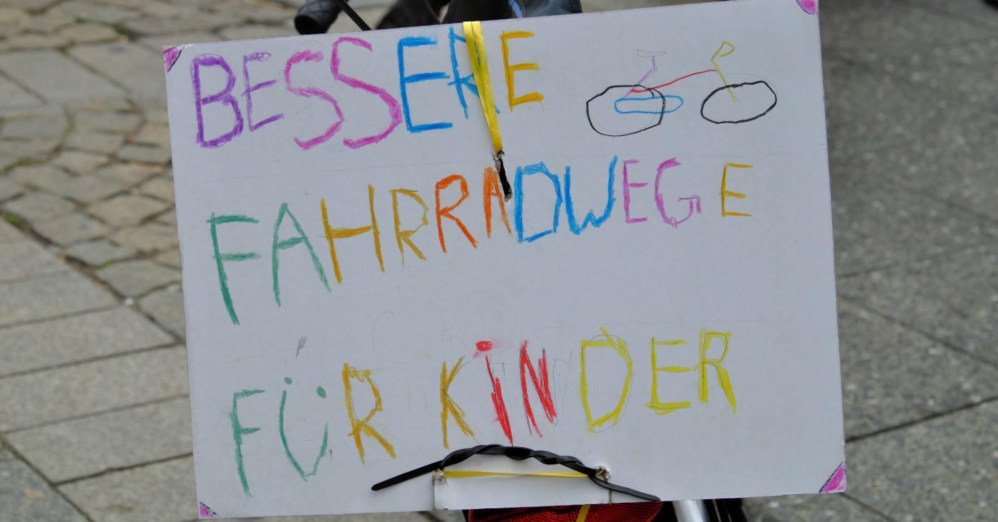 """Ein selbstgemaltes Schild auf dem steht: """"Bessere Fahrradwege für Kinder!"""