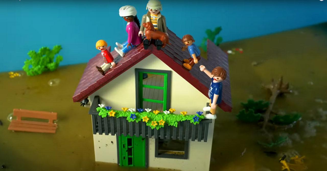 Ein Screenshot aus dem Mobiclip zum Klimastreik am 24. September 2021. Darauf ist ein Spielzeughaus mit Figuren zu sehen, die auf dem Dach sitzen, weil ein Hochwasser sie bedroht.