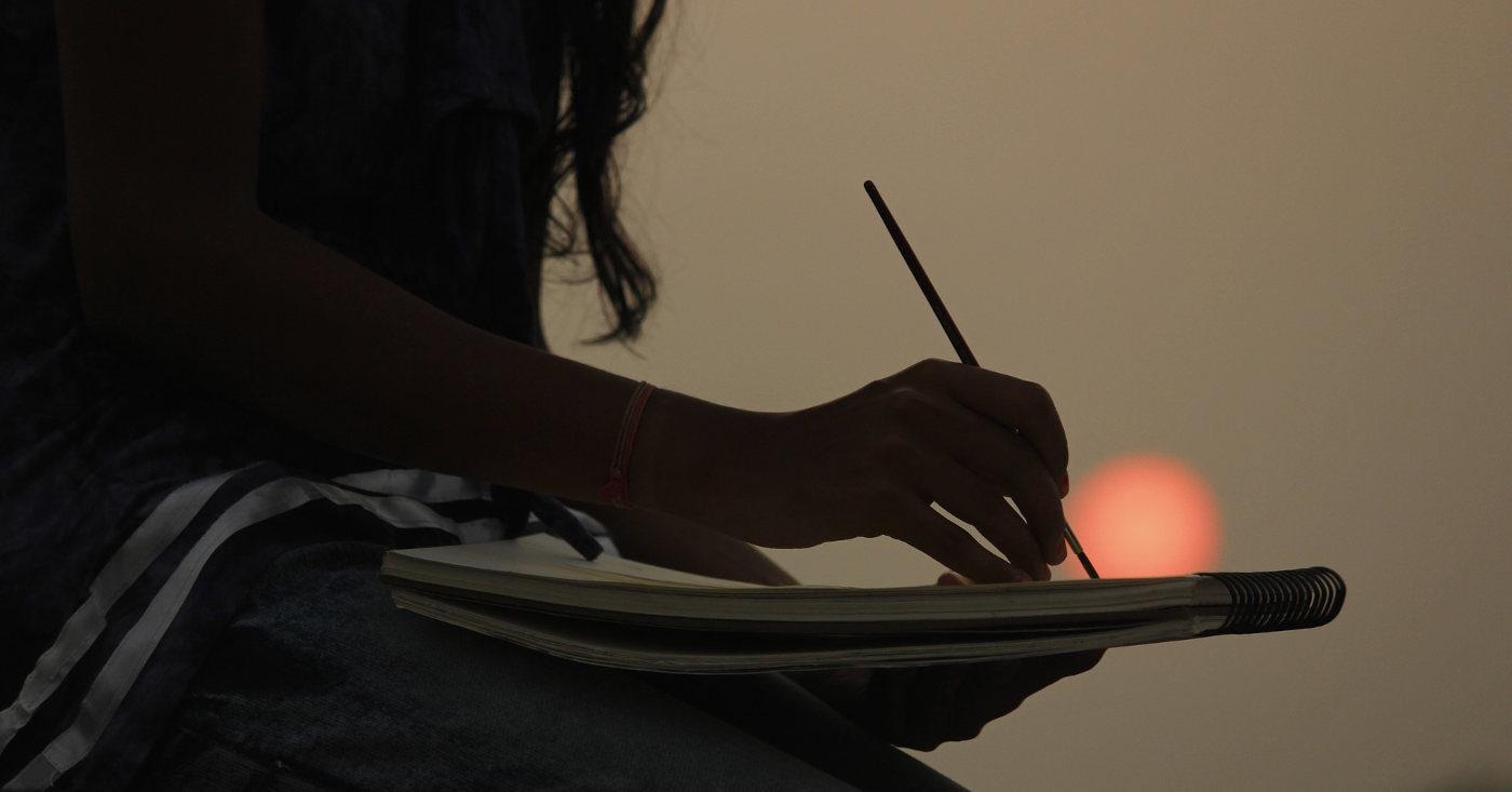 Eine Person malt etwas auf einen Skizzenblock. Im Hintergrund ist die untergehende Sonne zu sehen.